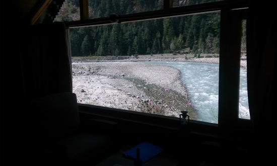 Banjara Camp &  Retreat - Sangla Valley Camp: View from the separate sitting area of the river facing log huts.