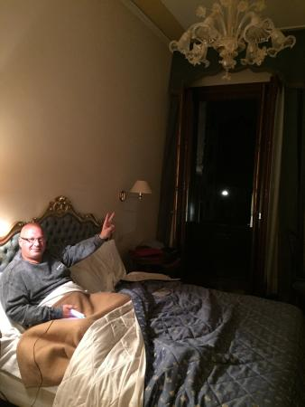 Locanda Sant'Agostin: my husband comfortably in bed as we listen to chatter outside... and steps on the old cobble...