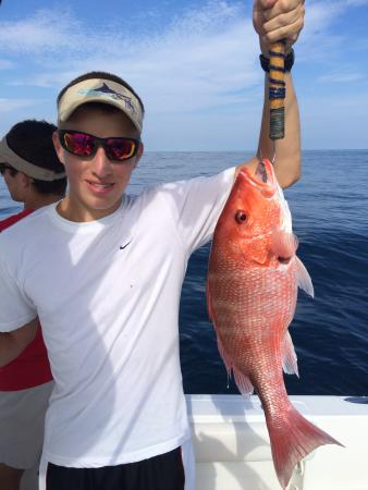 Son holds his first red snapper for Gulf angler fishing charters