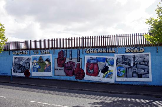 Tourists writing messages on peace line that divides for Belfast mural tours