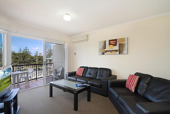 Labrador, Australia: Spacious lounge and dining room. Leather lounge suites. Tiled floors. Balcony off the lounge.