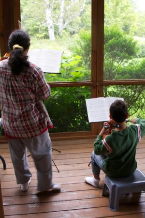Mount Holly, VT: Mother and son guests playing violins