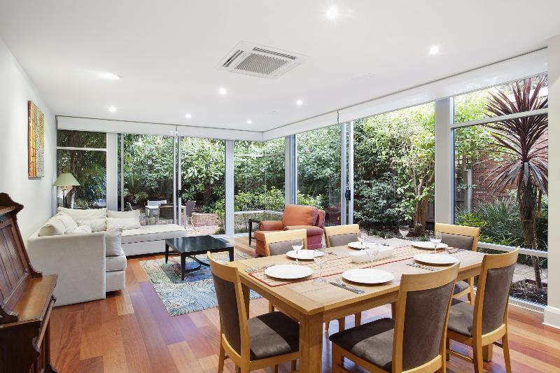 Spacious dining and informal living room overlooks rear garden and courtyard