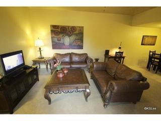 Spacious living room with flat screen TV and private patio