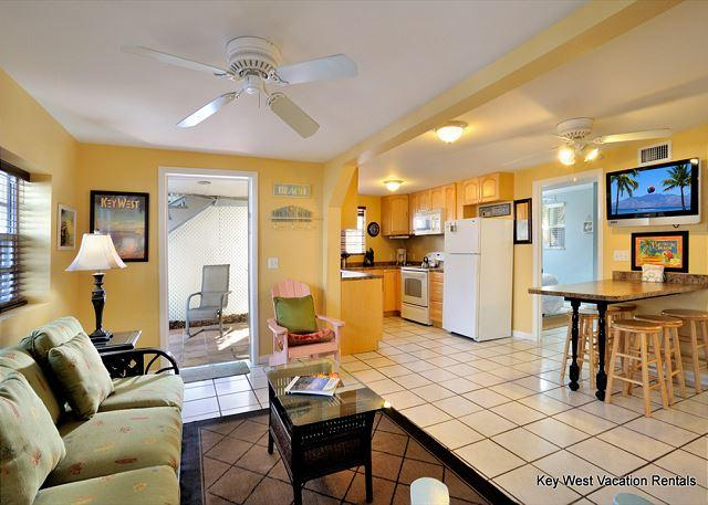 View From Living and Kitchen Areas Both Including Ceiling Fans and a View of the Flat Screen TV.  You can Also See the Dining Area, and Outdoor Space - Southernmost Retreat - Nightly - Key West - rentals