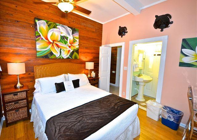 Spacious Queen Sized Bedroom With High Ceilings, Beautiful Tropical Decor and Wood Floors and Walls