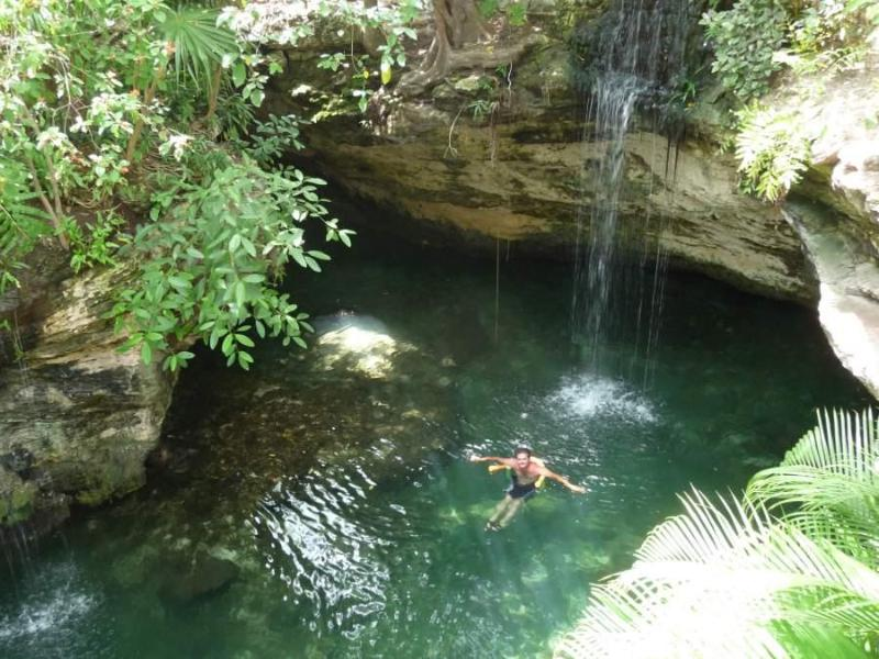 Refreshing private cenote with waterfall for swimming within condo complex
