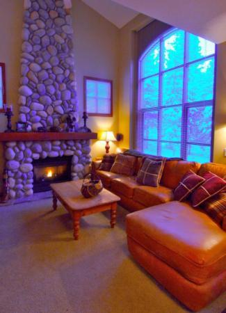 cosy living room with entertainment center and floor to ceiling stone fireplace