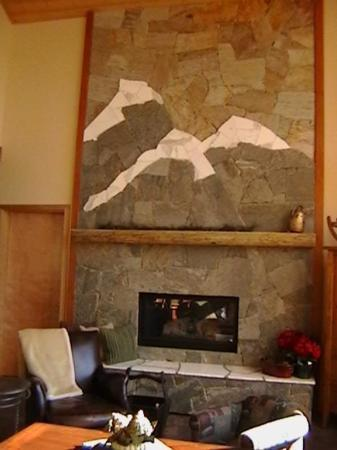 Custom stone fireplace with large seating area on hearth.