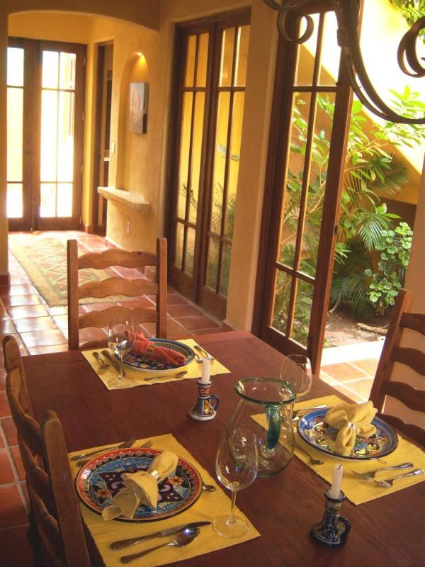 dining room table looking out onto the interior garden and small terrace with stone fountain.