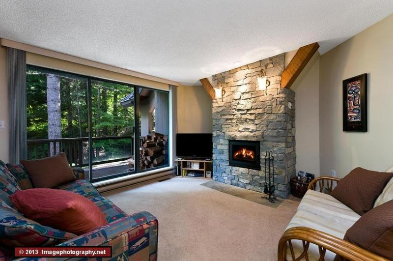 The townhouse has an open concept living area, with the living room, dining room and kitchen in the same space. Here is the sunken living room with a cosy fire and a view of the West Coast forest (with snow in winter!) outside. The aspect is quiet and pri