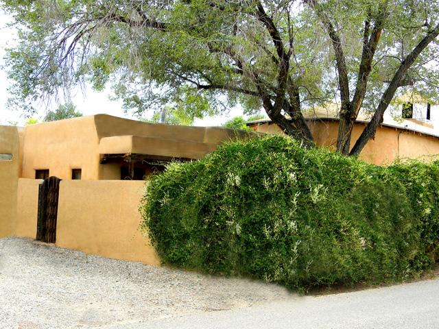 Front exterior with lush green flowering vines showing adobe walled enclosed private front yard