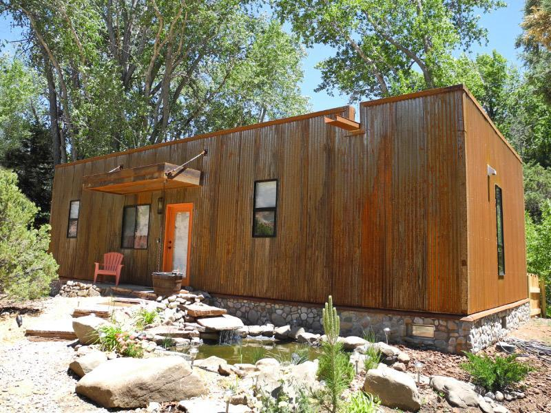 Taos Rio Eco Dwelling with pond waterfall and rusty steel siding/ river rock