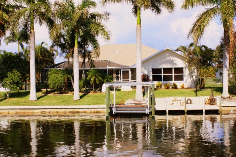 Canal View of Backyard with Mature Royal Palms Lining Seawall - Waterfront with a Private Pool