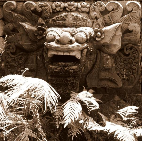 Hand-carved Stone Barong looks over the Koi and Lotus Pond