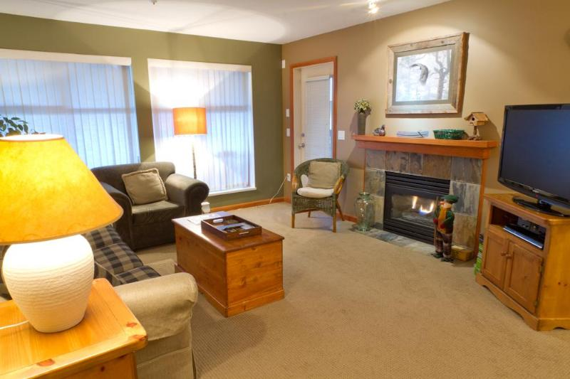 Living room with gas fireplace, flat scree TV and opens to a patio with BBQ