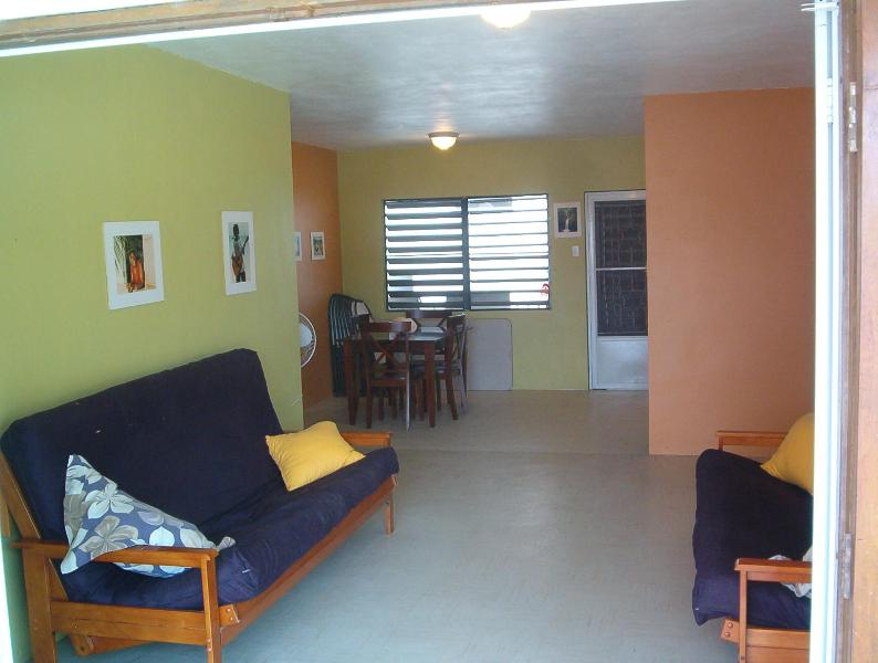 Living room with 2 queen sized sofa couches. The up has been repainted in bright tropical colors.