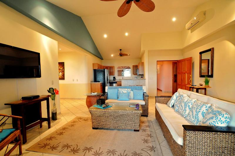 Main Living room with cozy sofas and full TV flat screen, kitchen at the back