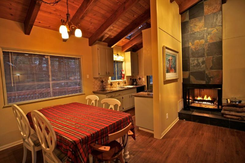Dining table with kitchen and wood burning fireplace in the background