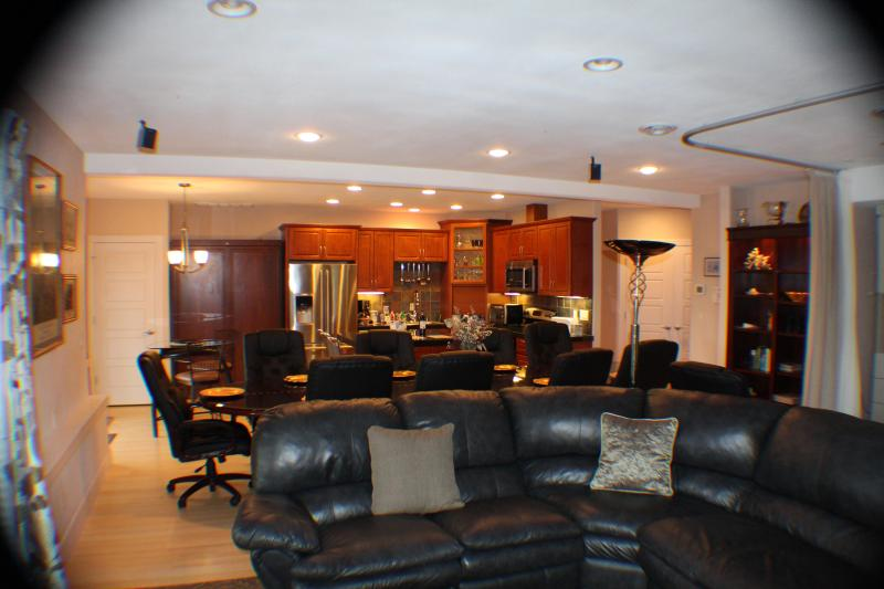 Living rom leather sectional with recliners into dining room and large kitchen