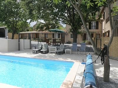 Another view of the swimming pool at Ginestas Gite. There is a large tiled patio area with seating f