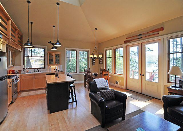Open floor plan features vaulted ceiling and view of the water.