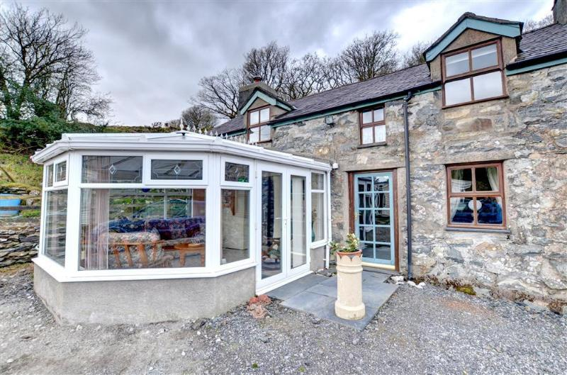 This substantial stone cottage has a large conservatory to the front