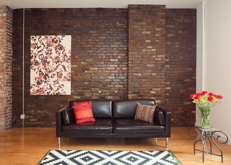 Exposed brick wall, original artwork, modern sofa in the living room