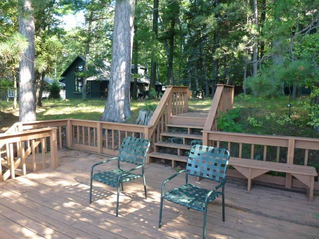 View of the private deck, which overlooks the lake, back to the cottage.  - Higgins  Lakefront cottage in deep woods - Higgins Lake - rentals