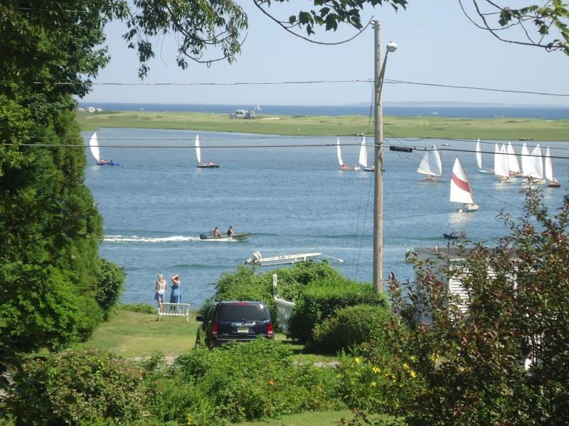view from deck across salt pond with ocean in the background and sailboats racing on a perfect day.