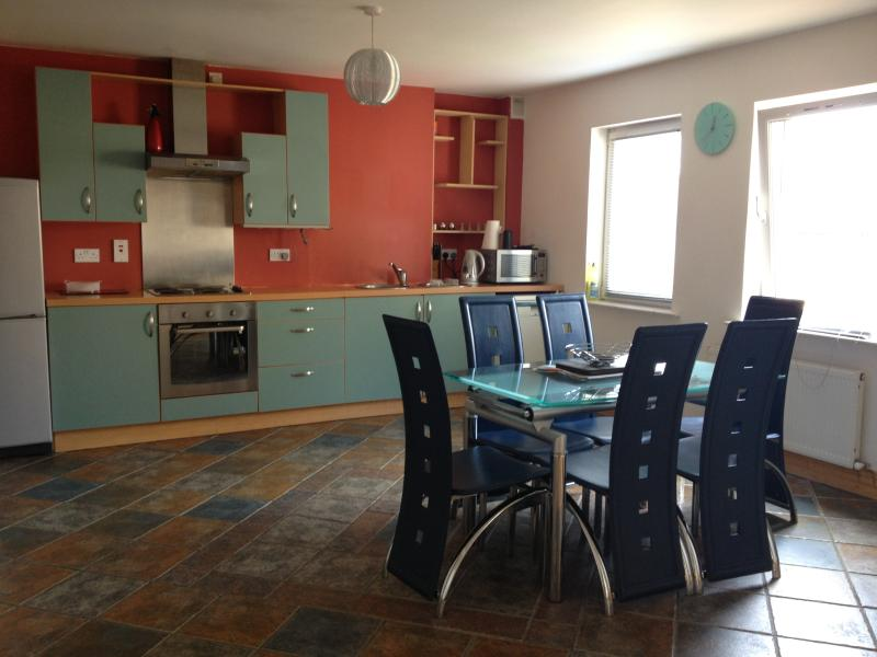 Fashionable Kitchen with dishwasher, fridge and stocked with utensils and cooking supplies