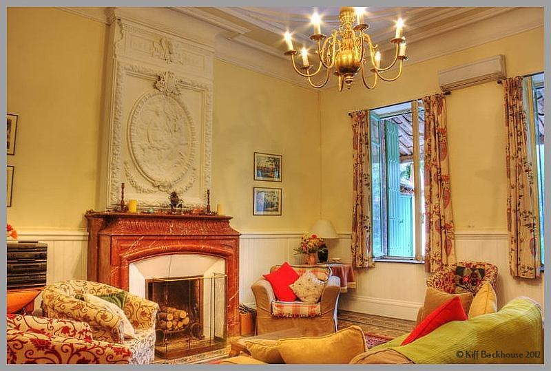 Grande House lounge with a comfy sofa and 3 armchairs. An old fashioned fireplace fits in well with