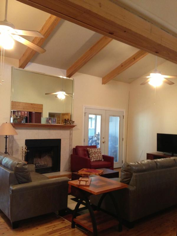 Vaulted wood beamed ceilings make this room spacious. Fireplace & ceiling fans