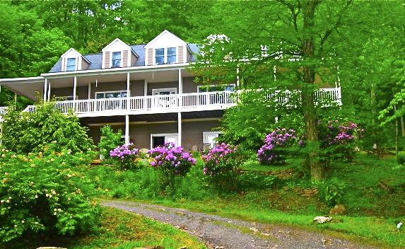 Bald Mountain House sitting creekside with long views of the Black Mountains including Mt. Mitchell.