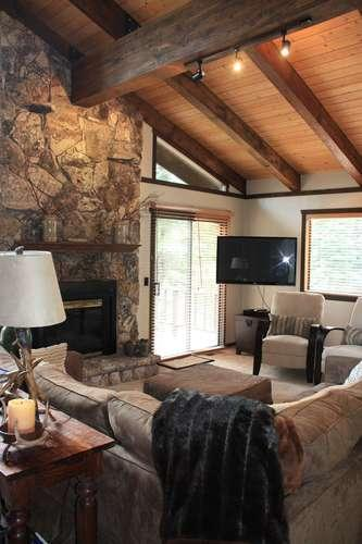 Great room of this lovely home with high ceilings, stone fireplace, upscale furnishings