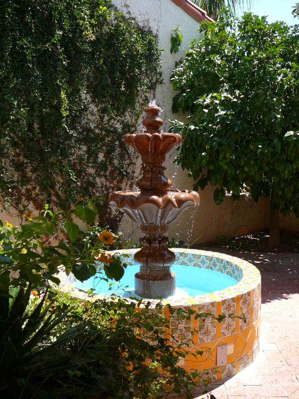 Entry courtyard - fountain designed of tiered stone and colorful Talavera Grapefruit & naval orange