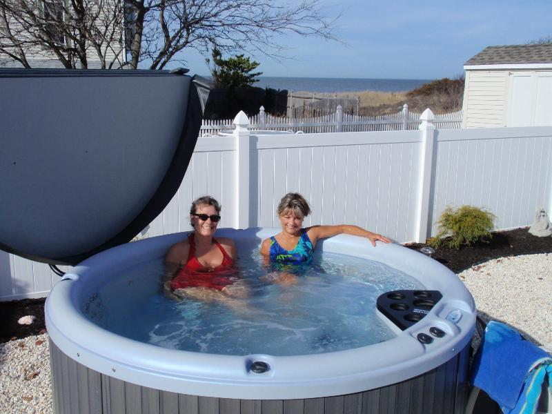6 person lighted hot tub showing partial bay view from deck