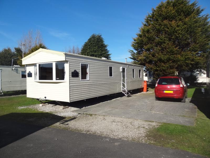 View of the caravan showing the outdoor space and car parking.
