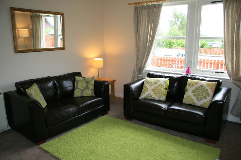 Lounge with twin leather sofas, TV, DVD player and Views to Mountains.