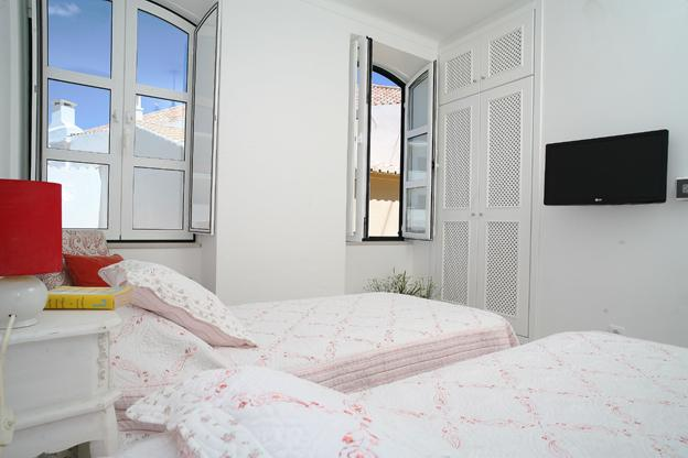 Light bedroom with TV and built in wardrobe