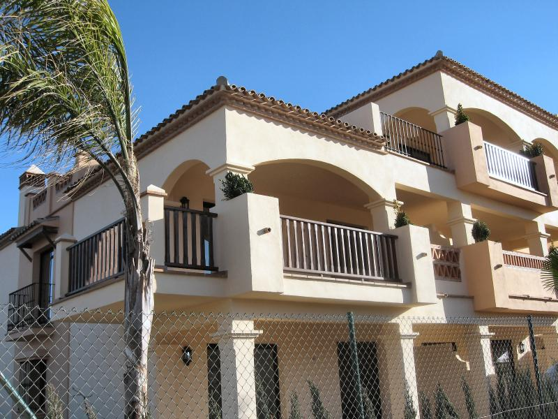 Front view with large corner balcony with views to the mountains and La Cala