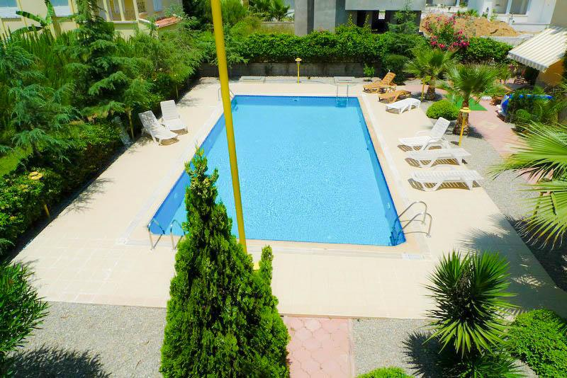 View of the large pool deck with mature garden