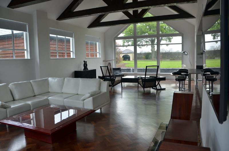 Beautiful open plan living area looking out onto spotlit garden, parquet floors