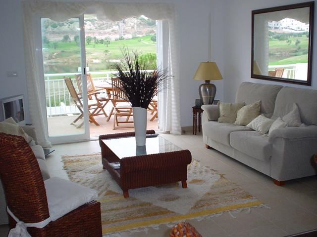 One view of lounge with balcony overlooking golf course and swimming pool.