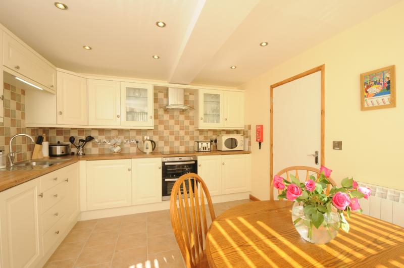 Kitchen with dining table situated in the Shop bay window giving excellent views of village life