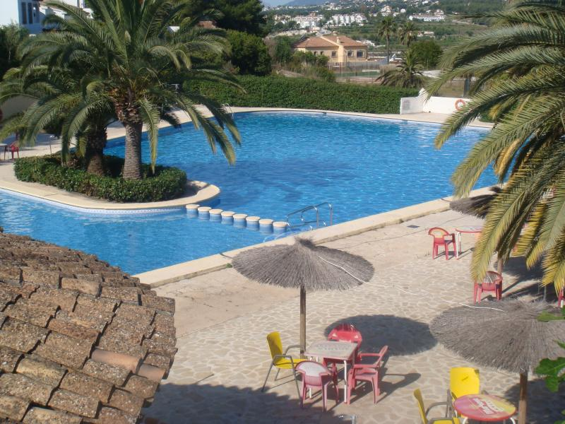 Pool with seating areas and sun parasols, a bar selling food, toilets and showers