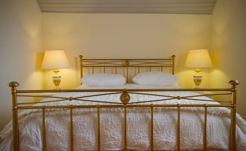 A romantic brass bed with 100% cotton sheets and a cosy mattress topper.