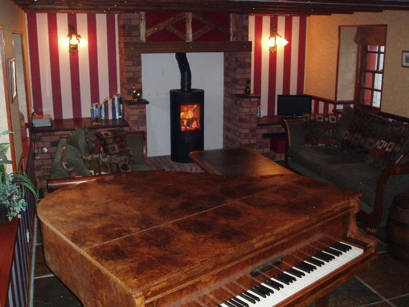 Cosy lounge with wood stove and baby grand piano