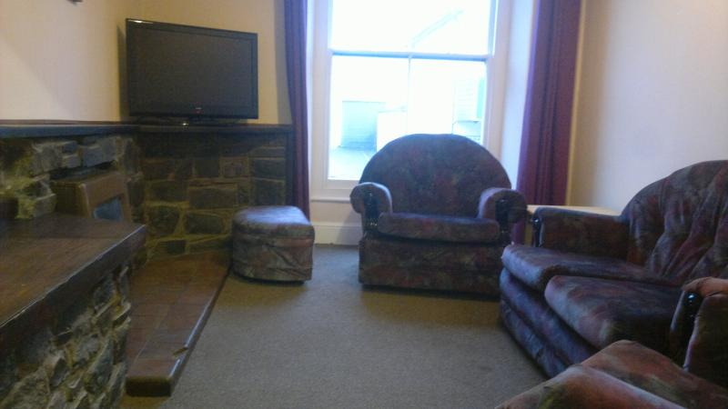 living room, with flat screen tv, parkray fire, leather sofa bed and chair.