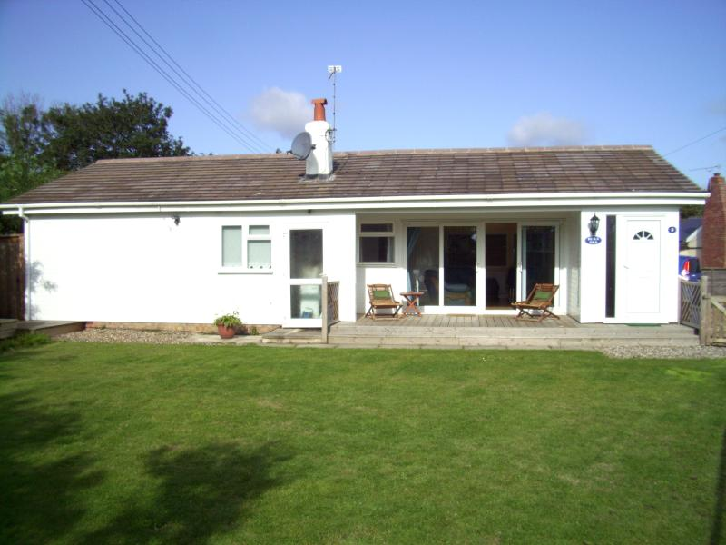 Front of bungalow showing decking and front lawn